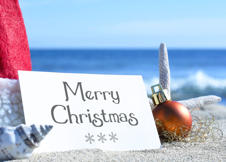 business christmas: Blank white card with christmas decoration and sea shell on a tropical beach. Christmas holidays. Greeting card with copyspace on the beach. Stock Photo