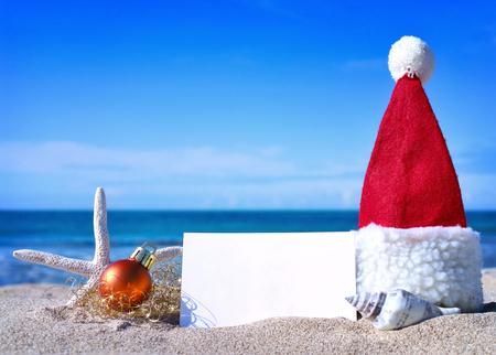 clima tropical: Tarjeta blanca en blanco con la decoración de navidad y concha de mar en una playa tropical. Vacaciones navideñas. Tarjeta de felicitación con copyspace en la playa. Foto de archivo