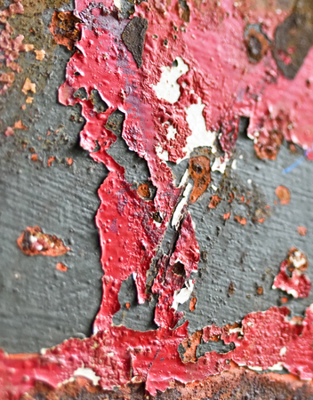 sullen: peeled paint on an old, weathered wall.