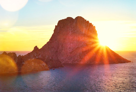 vedra: Sunset at Es Vedra, Ibiza Island. Sunbeam with lens flare behind the Isle of Es Vedra, magic rock of Ibiza. Stock Photo
