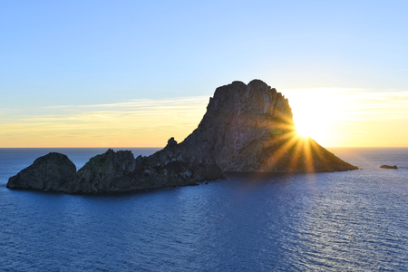 es: Sunset at Es Vedra, Ibiza Island. Sunbeam with lens flare behind the Isle of Es Vedra, magic rock of Ibiza. Stock Photo