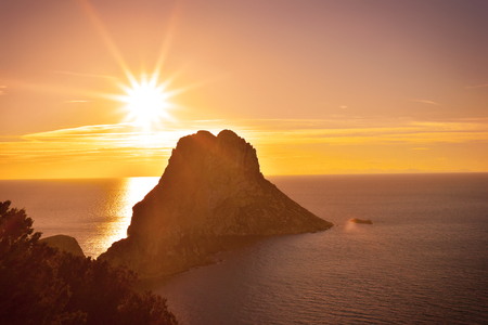 Sunset at Es Vedra, Ibiza Iceland. Sunbeam with lens flare behind the Isle of Es Vedra, magic rock of Ibiza.
