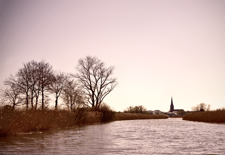 church tower: River scene with village and church tower at the horizon. Tranquil scene, scenic with bare trees and flowing water.