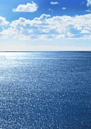 sparkling water: Seascape with sparkling water and fluffy clouds. Stock Photo