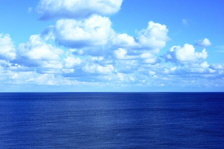 away from it all: Open water with copyspace. Sea scene and fluffy clouds.