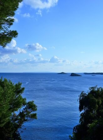 away from it all: Open water with copyspace. Sea scene and fluffy clouds. View through pine trees.
