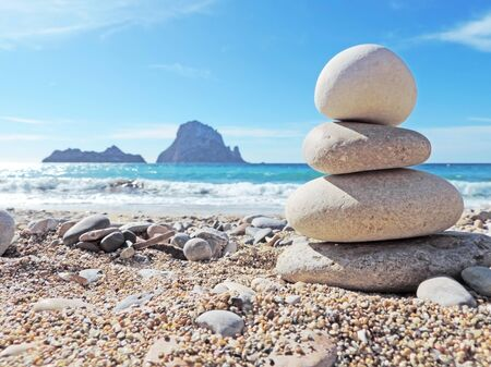 vedra: Balanced stones on the beach. View to the magic rock es Vedra in the background