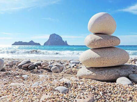 Evenwichtige stenen op het strand. Oog op de magische rots Es Vedra op de achtergrond