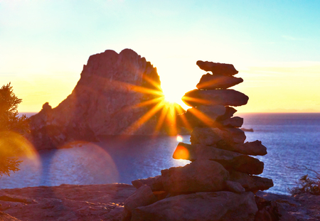 Sunset at Es Vedra with sunbeam. Sun shining through a stack rock on ibiza Iceland. Фото со стока