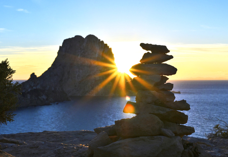 Sunset at Es Vedra with sunbeam. Sun shining through a stack rock on ibiza Iceland. Stock Photo