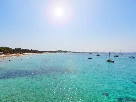 Beach scene with sunbeam and turquoise water.