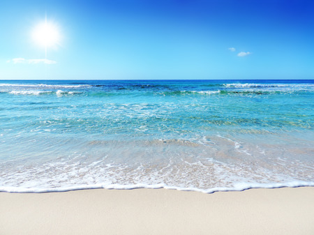 turquoise water: Tropical beach with waves and turquoise water. Sunbeam and gently rolling waves.
