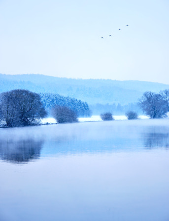 snowlandscape: Winter scene at a river with fog and bare trees.
