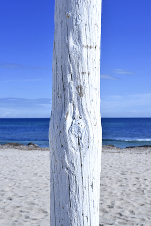 white pole: white flagpole on the beach. selective focus of a white pole on a sunny beach with blue sky and white sand. Stock Photo