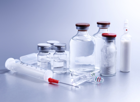 exhilaration: Vials and syringe, studio shot. Medical objects for vaccination. Vaccine drew up into a syringe.