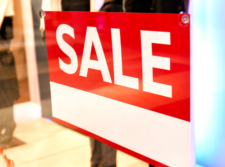 retail place: Sale sign in a shopping mall. Looking inside of a store window. Stock Photo