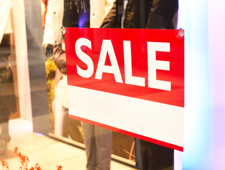 looking inside: Sale sign in a shopping mall. Looking inside of a store window. Stock Photo