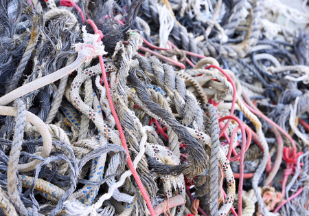 nautical   vessel: Tangled, old ropes. Stack of old, weathered ropes with selective focus. Close-up of nautical vessel. Chaos scene.