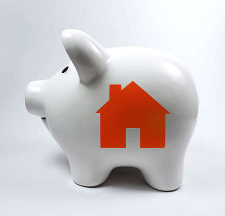 White porcelain piggybank with house, symbol Stock Photo