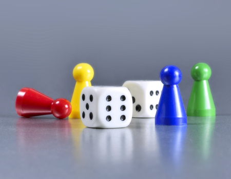 Playing pieces and dice, isolated gray background Stock Photo