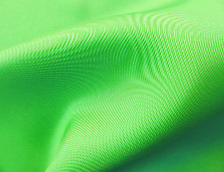 Green cloth or textile, wavy textile, close-up shot.
