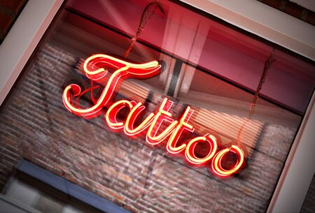 window display: Red tattoo sign in a shop window, close-up shot Stock Photo