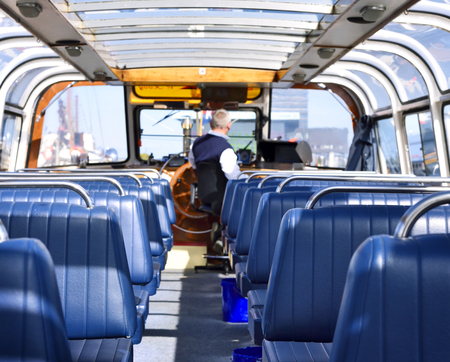 Indoors of a tourboat with blue seats.