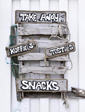 letreros: Driftwood letrero de un club de playa con caf� y bebidas para llevar. Primer plano de letreros de madera en un club de playa. Foto de archivo