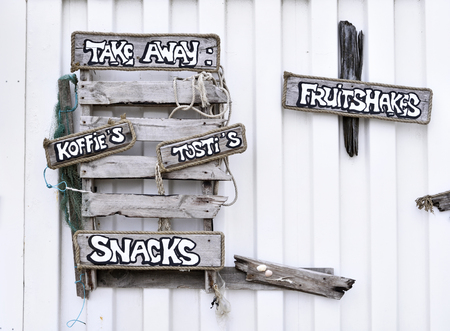 letreros: Driftwood signboard of a beach club with coffee and drinks to go. Close-up of wooden signboards at a beach club. Foto de archivo