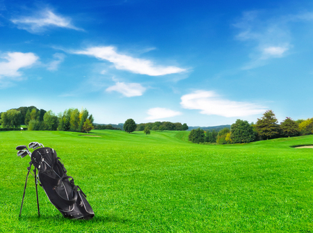 golf bag: Idyllic golf course with forest and golf bag in the foreground. Stock Photo