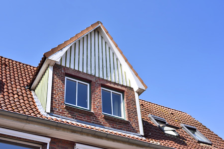 Old brick stone house with dormer and clear blue sky. Stock Photo