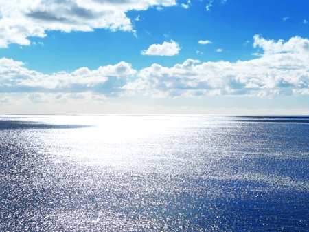 sparkling water: Sea scene with sparkling water and fluffy cloudscape.