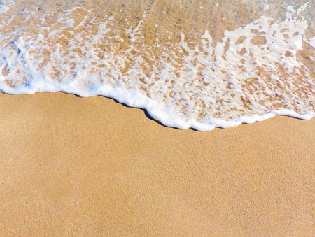 water's edge: Close-up of sand and surf on the beach. beach or sand texture. Sand background with copy space.