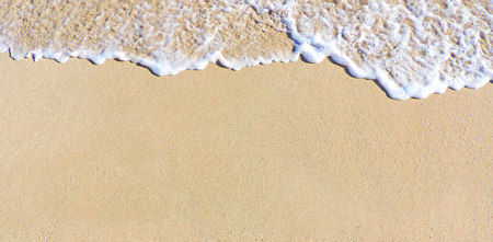 Close-up of sand and surf on the beach. beach or sand texture. Sand background with copy space.