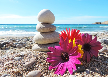 Stack of pebbles on a beach rock, decorated with multicolored flowers.