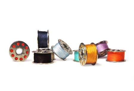 Sewing bobbins of various colors, isolated on white background. Stock Photo
