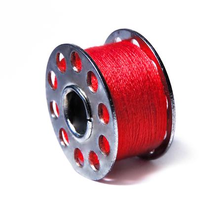hilo rojo: hilo rojo en una bobina de costura, aislado en blanco.