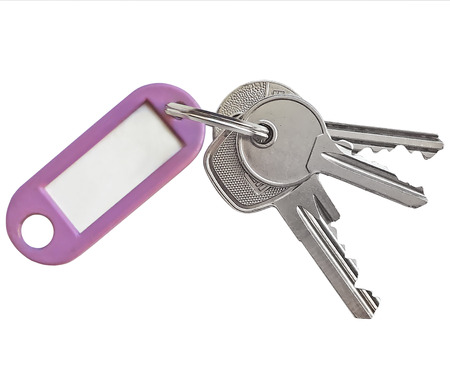 Key ring with silver keys and blank name tag with copy space, isolated on white background.