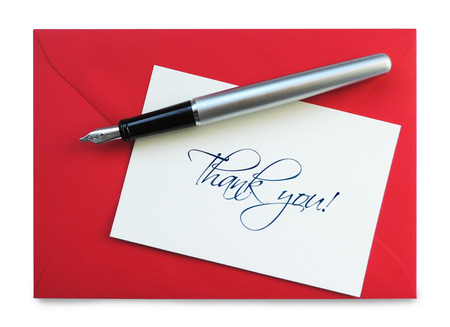 Thank you card on a red envelope with silver fountain pen, isolated on white.