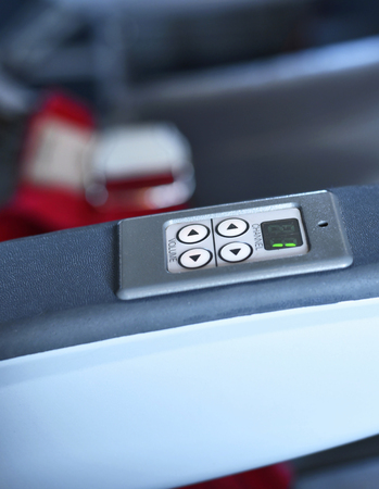 ooking: Arm rest of an airplane seat, board entertainment. Stock Photo