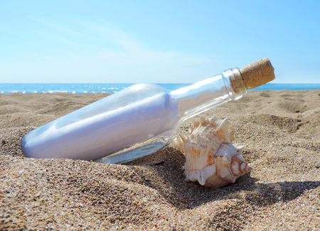 Message in a bottle, washed ashore the beach. Close-up.
