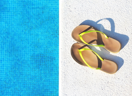 swimming shoes: Flip flops on a pool, vacations scene with copy space.