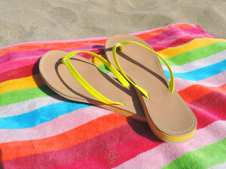beach towel: Flip flop shoes on the beach with multicolored beach towel.