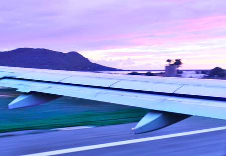 taking off: Airplane taking off into the sunset with purple sky. Stock Photo