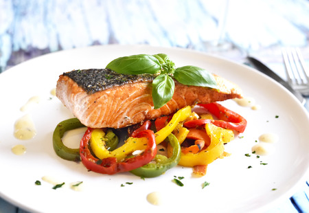 Delicious salmon filet and red bell pepper vegetables on a white plate. Healthy meal, decorated with basil leaf. Stock Photo