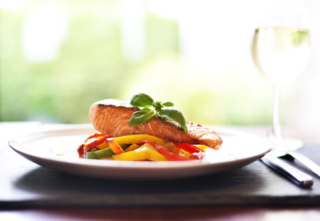 Delicious salmon filet with decorative basil leaf and multicolored peppers or bell pepper vegetable. Healthy eating scene.