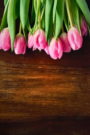 darkwood: Flower bouquet of pink tulips on a wooden table or wooden planks. Spring background with copy space and pink spring flowers.