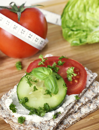 Healthy eating or dieting scene with crispbread and fresh tomatoes and cucumber. Tape measure and wooden table.