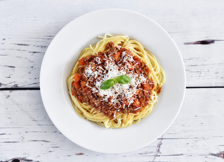 Spaghetti bolognese on a white plate with decorative basil leaf. Italian cuisine, pasta with tomato sauce and parmesan cheese.