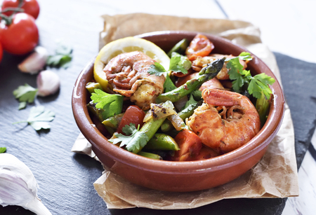 Fresh jumbo shrimps and green asparagus, delicious dish or meal, close-up shot. Spanish tapas. Stock Photo